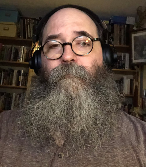 Selfie, in the study, without smile, with wild quarantine beard.